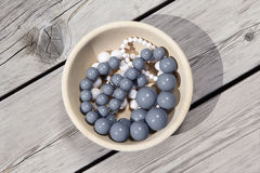 Beads in bowl. Сolored beads in the wooden bowl on the wooden floor Stock Photography