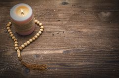 Beads and burning candle. Religion background. Beads and burning candle on wooden table background with copy space. Meditation stock image