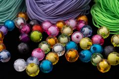 Beads, colorful beads on a black background. Elastic rope on the background. royalty free stock photography