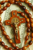 Beads with cross on dollars. Beads with wooden cross lying on one hundred dollars Royalty Free Stock Photo