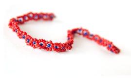 beads det blåa armbandet som göras red Fotografering för Bildbyråer