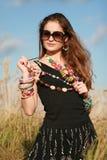 beads flickaholdingsolglasögon Arkivfoto