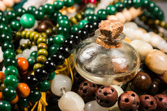 Beads and glasses. Small glass bottles and beads on a gray background Stock Image