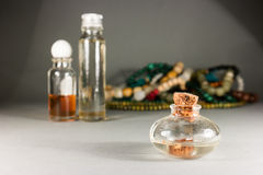 Beads and glasses. Small glass bottles and beads on a gray background Stock Photos