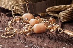 Beads, golden chain, golden cloth an leather belt stock photos