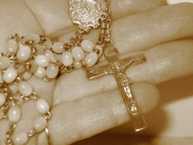 Beads in hand. Rosary beads in hand, sepia tone stock images