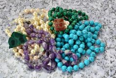 Beads from malachite, amethyst, pearls and turquoise close up. Beads from malachite, amethyst, pearls and turquoise, a brooch from a red jasper close up on a stock photo