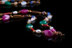 Beads with multi-colored stones on a black background Royalty Free Stock Image