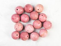 Beads from natural pink rhodonite gemstone. Top view of beads from natural pink rhodonite gemstone on gray concrete background stock images
