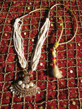 Beads necklace. Indian beads and pearl necklace on a red glittering fabric Stock Images