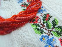 Beads necklace on authentic ukrainian embroidery shirt with lace. Royalty Free Stock Photo