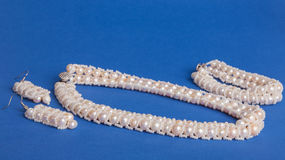 Beads and pearls on blue background Stock Photo