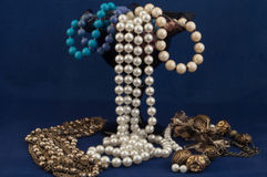 Beads And Pearls. Overflowing from a purple vase Stock Photo