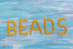 Beads. Text written in orange  on a wooden background Royalty Free Stock Images