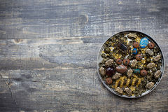 Beads into tin lid. Small beads into tin lid on wooden background Royalty Free Stock Images