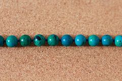 Beads from turquoise lie on a box of cork tree stock image