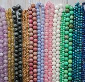 Beads from various natural stones are strung on threads. royalty free stock photography