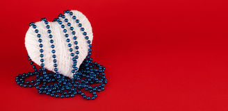 Beads on a white heart made of wool Royalty Free Stock Image