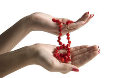 Beads in woman hands. Two hands with a red beads. Isolated on white background stock photo