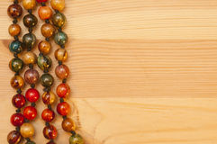 Beads on a wooden background Royalty Free Stock Images