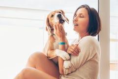 Beagle pies i sw?j w?a?cicieli u?ci?ni?cia na pogodnym tarasie zdjęcia stock