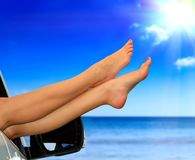 Beaitiful female legs against the sea and summer blue sky. Stock Image