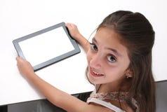 Beaitiful pre-tonårig flicka som använder en minnestavladator Arkivbild