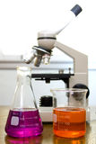 Beaker, flask and blured microscope Stock Photos