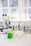 Beakers with chemical fluid and microscope Royalty Free Stock Photography
