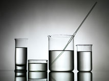 Beakers with dropper and transparent liquid substance Royalty Free Stock Photos