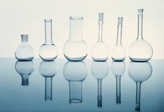 Beakers. Many of the beakers are in a row in the backlight, the reflection, the blue background