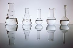 Beakers. Many of the beakers are in a row in the backlight, the reflection, the blue background. with liquid