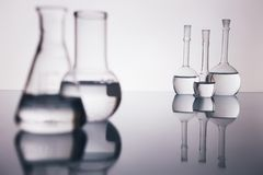 Beakers. Many beakers are in row, with liquid, in backlight, reflection, blue background