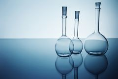 Beakers. Three beakers in backlight, reflection, blue background