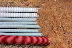 Beam corrugated underground conduits covered with sand royalty free stock images