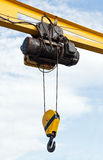 Beam crane with engine and hook hanging on ropes Stock Photos