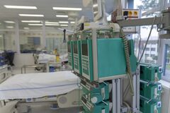 Beam with infusion pumps and syringe pumps, on background beds in ICU in hospital, a place where can be  treated patients with