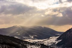 Beam of light through cloudy sky over the mountain. Lovely winter landscape stock photo
