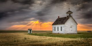 Old Abandoned Church at Sunset. A beam of light shines down on an old abandoned church in a field royalty free stock photo