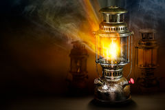 Beam of light from storm lantern. Beam of light and fire blaze with smoke from vintage rusty steel storm lantern on dark background Stock Images