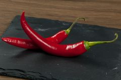 Beam of red chilli pepper on black background. royalty free stock photography
