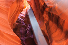 Beam of sun ray and dust between colorful sandstone walls of Upper and Lower Antelope Canyon near Page Arizona Stock Images