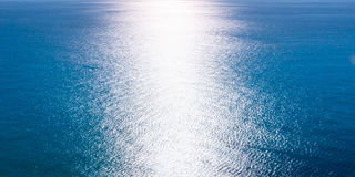 A beam of sunlight reflecting over rippled dark blue water Royalty Free Stock Photos