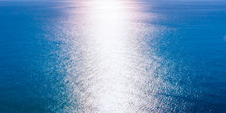 A beam of sunlight reflecting over rippled dark blue water. Toned. Stock Images