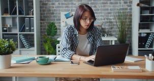 Beambte die laptop met behulp van die dan in notitieboekjezitting bij bureau in werkplaats schrijven stock videobeelden