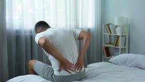 Beambte die scherpe pijn in rug voelen die van bed, sedentaire levensstijl weggaan stock video