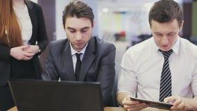 Beambten die laptop en het bespreken bekijken stock videobeelden
