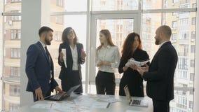 Beambten, werknemers van een groot bedrijf, twee jonge mannen en drie jonge vrouwen die zich dichtbij de lijst met documenten bev stock videobeelden