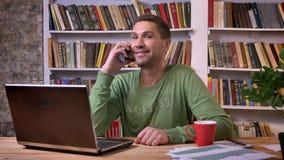 Beambtezitting voor laptop en het spreken op een telefoon met warme gelaatsuitdrukking Boekenrekken op de rug stock footage