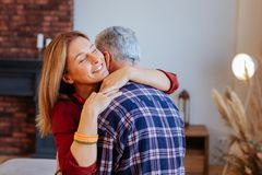 Beaming appealing woman feeling memorable hugging husband. Feeling memorable. Beaming appealing women feeling memorable hugging husband after romantic evening royalty free stock photos